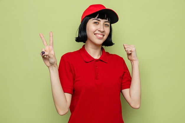 Souriante jeune livreuse caucasienne gardant le poing et gesticulant le signe de la victoire