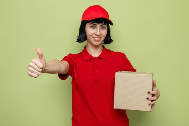 Souriante jeune livreuse caucasienne tenant une boîte en carton et levant le pouce