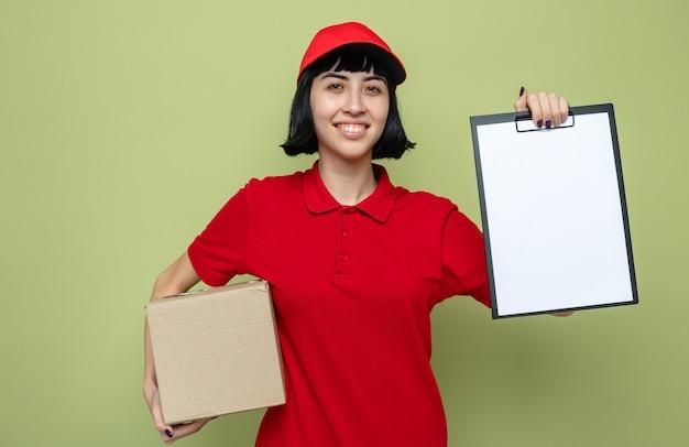 Souriante jeune livreuse caucasienne tenant une boîte en carton et un presse-papiers