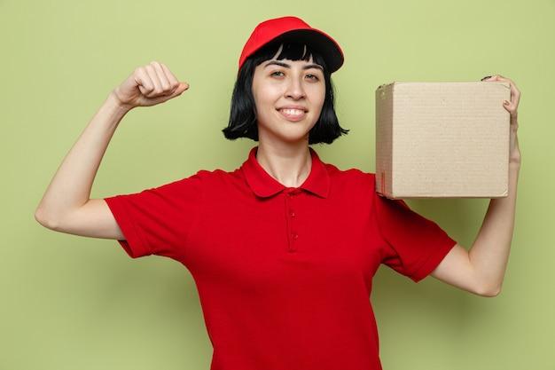 Souriante jeune livreuse caucasienne tenant une boîte en carton et tendant ses biceps