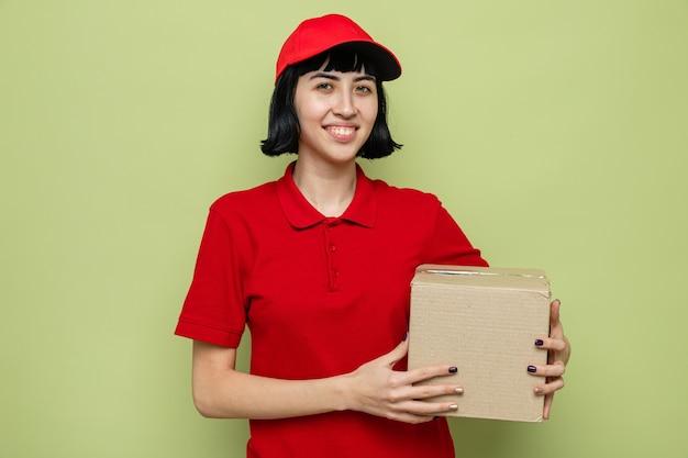 Souriante jeune livreuse caucasienne tenant une boîte en carton