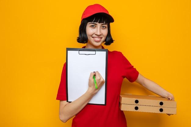 Souriante jeune livreuse caucasienne tenant des boîtes à pizza et un presse-papiers