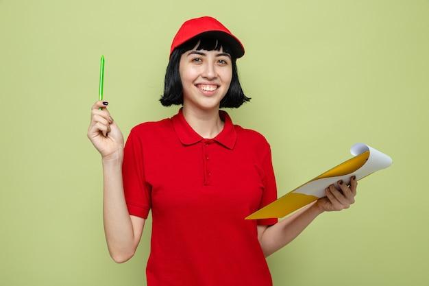 Souriante jeune livreuse caucasienne tenant un presse-papiers et un stylo