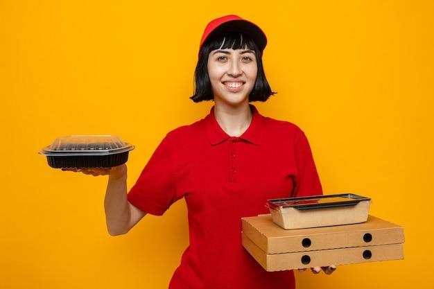 Souriante jeune livreuse caucasienne tenant un récipient de nourriture et un emballage sur des boîtes à pizza