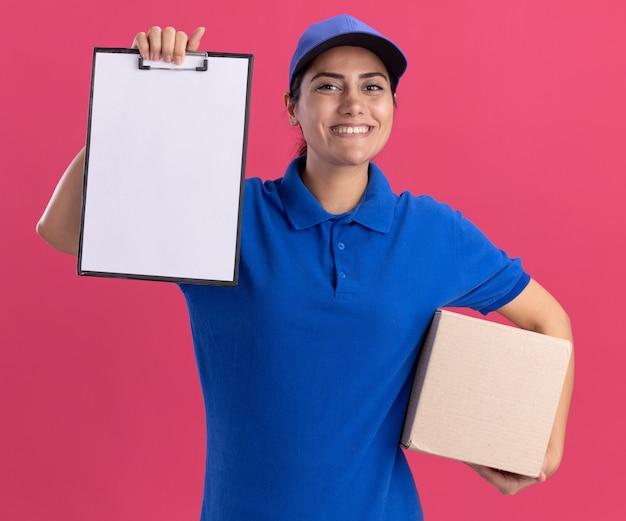 Souriante jeune livreuse en uniforme avec capuchon soulevant la boîte de maintien du presse-papiers isolé sur le mur rose