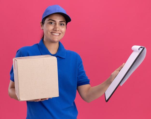 Souriante jeune livreuse en uniforme avec capuchon tenant la boîte avec presse-papiers isolé sur mur rose