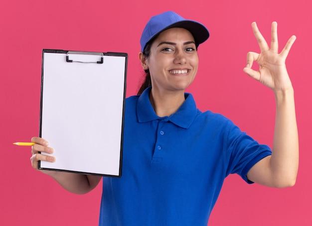 Souriante jeune livreuse en uniforme avec capuchon tenant le presse-papiers et montrant le geste correct isolé sur le mur rose