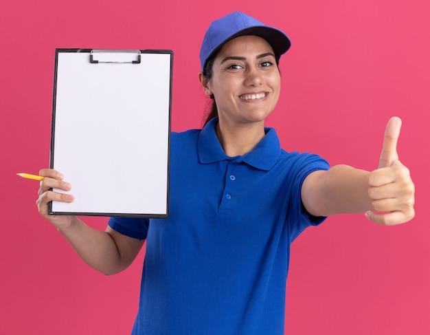 Souriante jeune livreuse en uniforme avec capuchon tenant le presse-papiers et montrant le pouce vers le haut isolé sur un mur rose