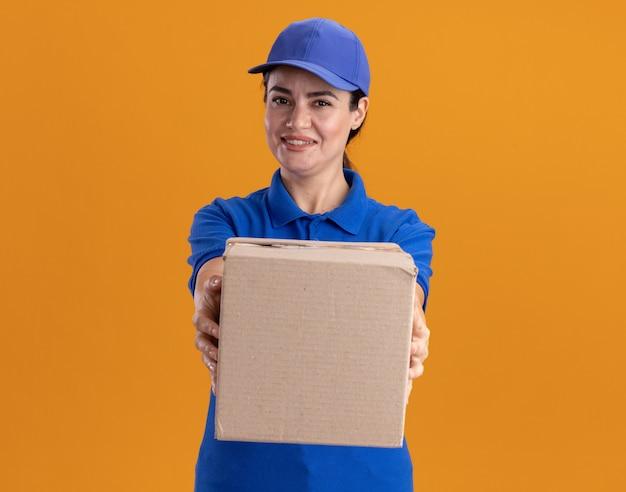 Souriante jeune livreuse en uniforme et casquette avec boîte en carton