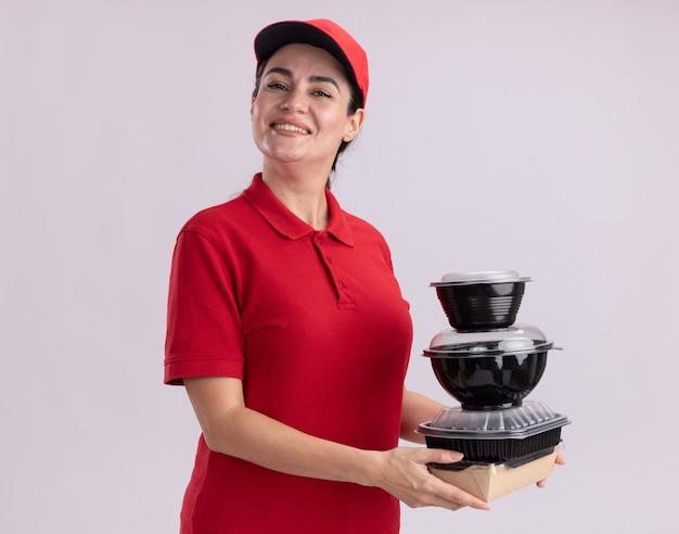 Souriante jeune livreuse en uniforme et casquette debout en vue de profil tenant un emballage alimentaire en papier et des récipients alimentaires