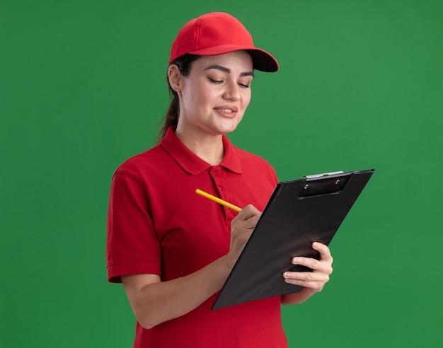 Souriante jeune livreuse en uniforme et casquette écrivant sur le presse-papiers avec un crayon isolé sur le mur