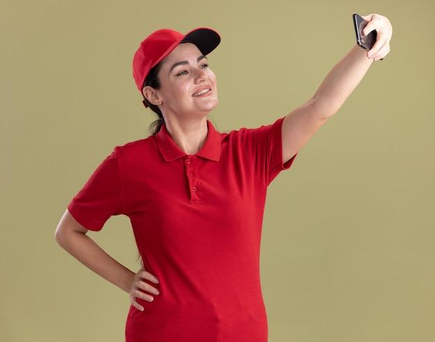 Souriante jeune livreuse en uniforme et casquette gardant la main sur la taille prenant un selfie isolé sur un mur vert olive