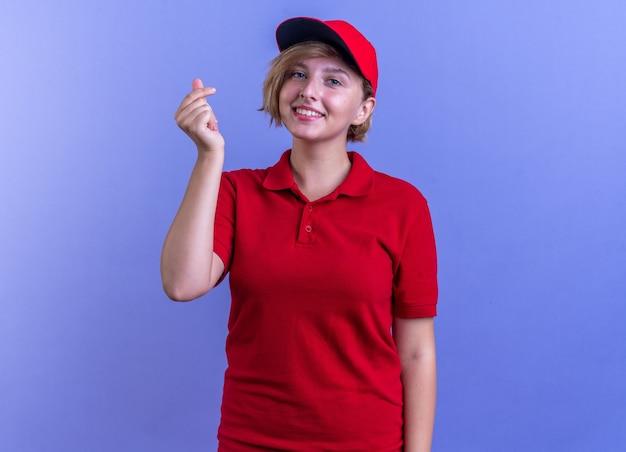 Souriante jeune livreuse en uniforme et casquette montrant un geste de pointe isolé sur un mur bleu
