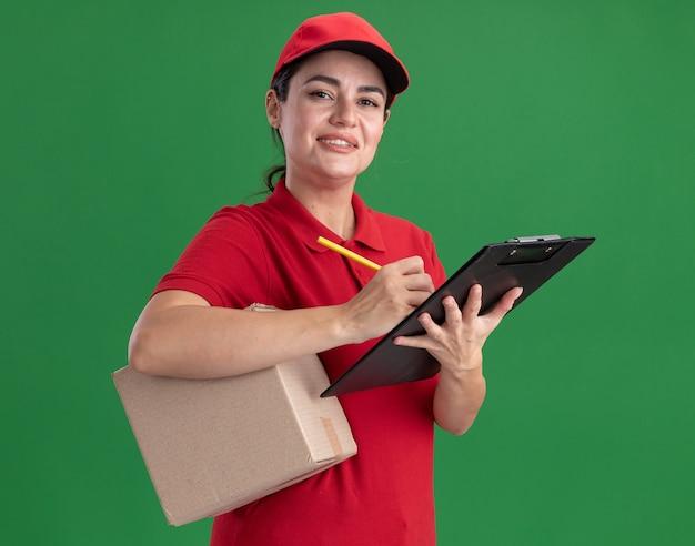 Souriante jeune livreuse en uniforme et casquette tenant une boîte en carton et un presse-papiers avec un crayon
