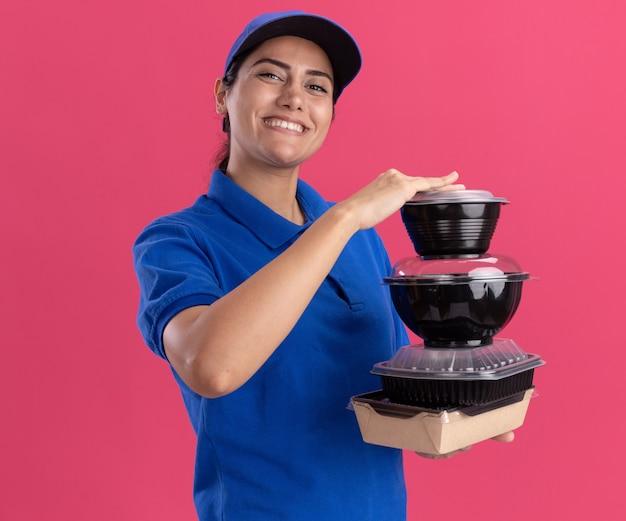 Souriante jeune livreuse en uniforme avec casquette tenant des récipients alimentaires isolés sur un mur rose