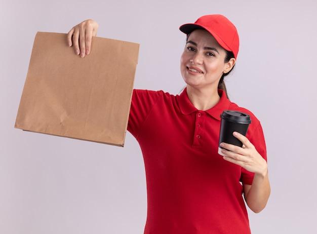 Souriante jeune livreuse en uniforme et casquette tenant une tasse à café en plastique et un paquet de papier