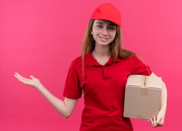Souriante jeune livreuse en uniforme rouge tenant la boîte et montrant la main vide sur l'espace rose isolé