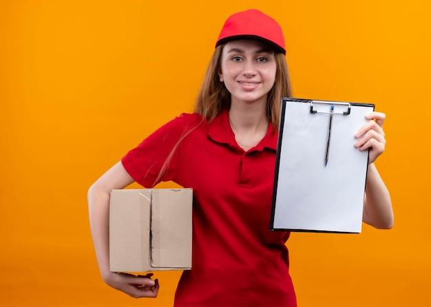 Souriante jeune livreuse en uniforme rouge tenant la boîte et montrant le presse-papiers sur l'espace orange isolé