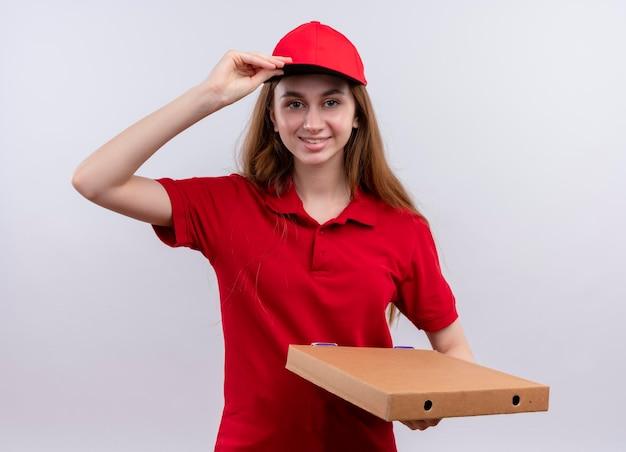 Souriante jeune livreuse en uniforme rouge tenant le paquet et mettant la main sur le capuchon sur un espace blanc isolé