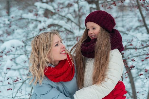 Souriante jeune mère et sa jolie fille patinage sur glace ensemble à la main.