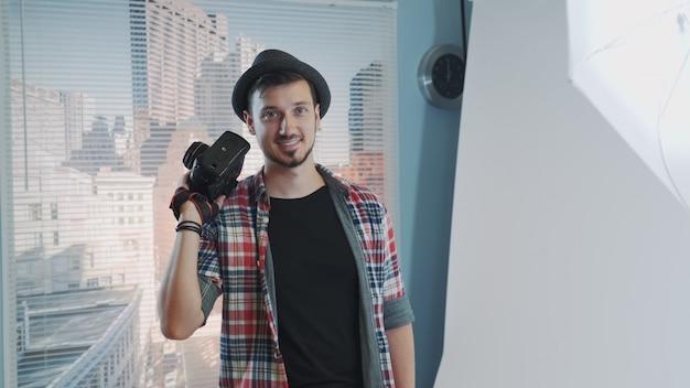 Souriante jeune photographe posant avec son appareil photo professionnel.