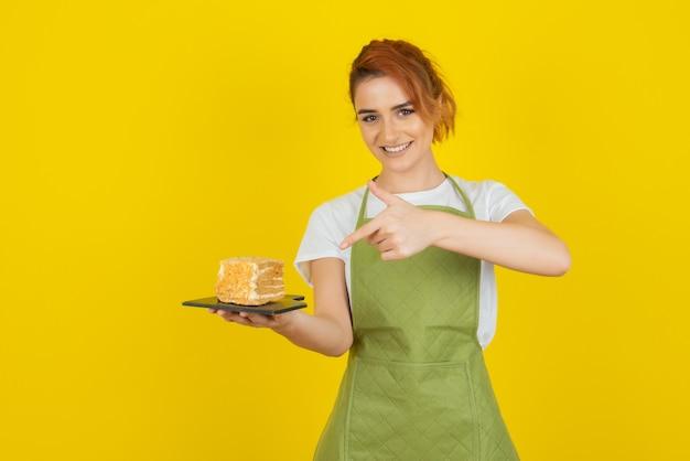 Souriante jeune rousse pointant le doigt sur une tranche de gâteau frais