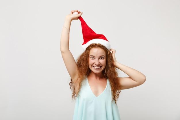 Souriante jeune rousse santa girl dans des vêtements légers posant isolé sur fond de mur blanc, portrait en studio. concept de vacances de célébration de bonne année 2020. maquette de l'espace de copie. tenant le chapeau de noël.