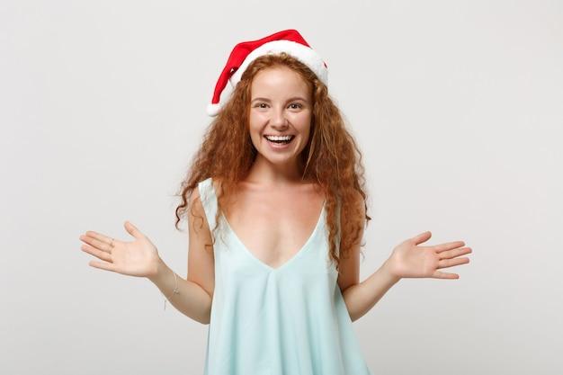 Souriante jeune rousse santa girl en vêtements légers, chapeau de noël isolé sur fond blanc, portrait en studio. concept de vacances de célébration de bonne année 2020. maquette de l'espace de copie. écartement des mains.