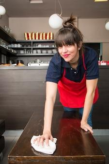 Souriante jeune serveuse femme nettoyant la table avec une serviette