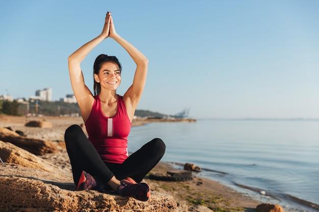 Souriante jeune sportive assise en position d'yoga