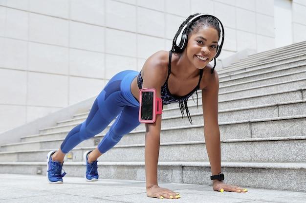 Souriante jeune sportive noire faisant des pompes à l'extérieur après le jogging