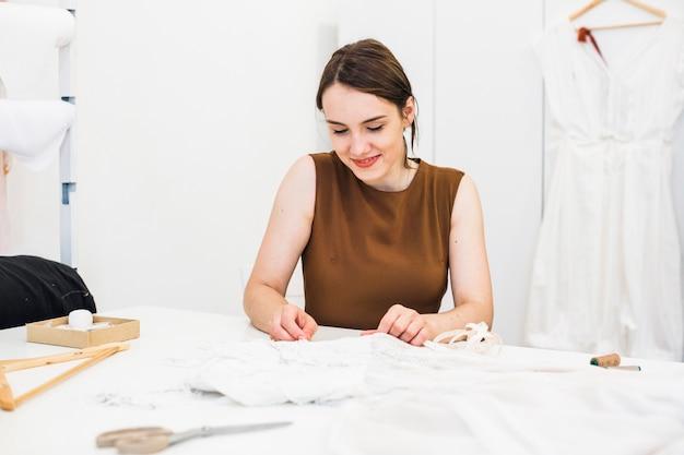Souriante jeune styliste travaillant sur la robe en studio