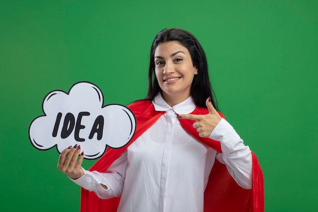 Souriante jeune superwoman tenant la bulle d'idée et pointant son index vers elle à l'avant isolé sur mur vert