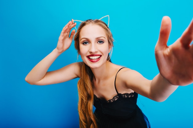 Souriante jolie blonde aux yeux bleus posant, prenant selfie, profitant de la fête. porter une robe noire et un bandeau avec des oreilles de chat.