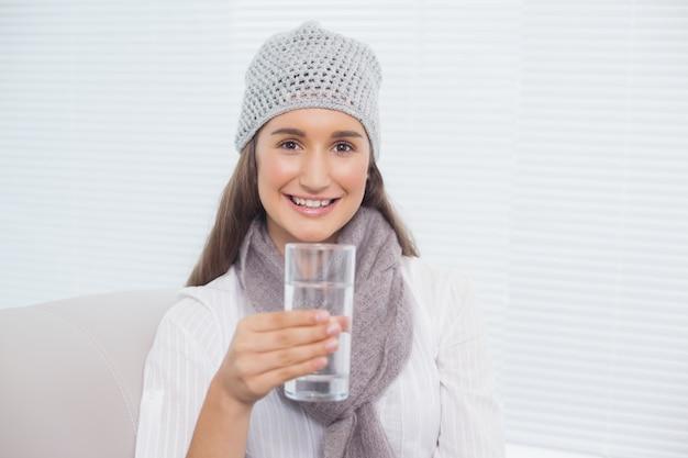 Souriante jolie brune avec un chapeau d'hiver sur tenant le verre d'eau