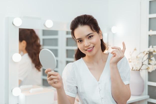 Souriante jolie brune tenant un miroir dans une chambre lumineuse