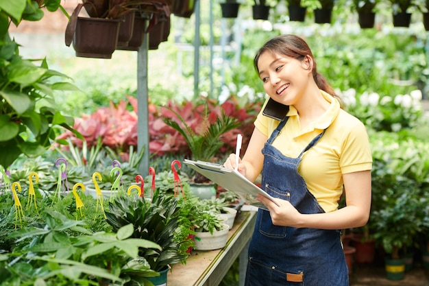 Souriante jolie employée du centre de jardinage parlant au téléphone avec le client et prenant des notes dans un document
