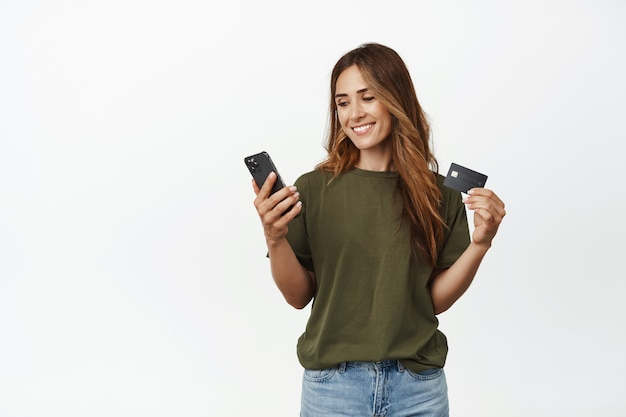 Souriante jolie femme d'âge moyen, tenant une carte de réduction de crédit, regardant l'écran du smartphone