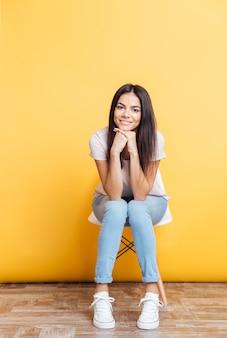 Souriante jolie femme assise sur la chaise sur backgorund jaune