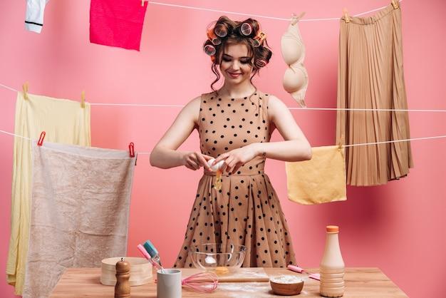 Souriante, jolie femme au foyer brune cuisine sur fond de cordes avec des vêtements sur un mur rose. la femme casse un œuf, les ustensiles de cuisine sont debout.