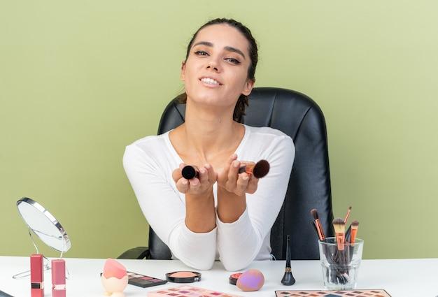 Souriante jolie femme caucasienne assise à table avec des outils de maquillage tenant des pinceaux de maquillage isolés sur un mur vert olive avec espace de copie