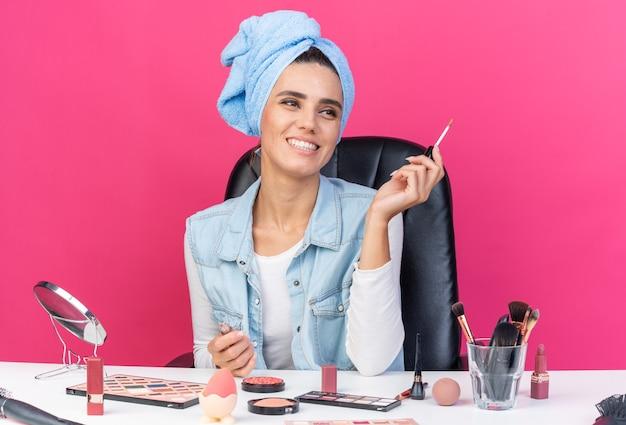 Souriante jolie femme caucasienne aux cheveux enveloppés dans une serviette assise à table avec des outils de maquillage tenant un brillant à lèvres isolé sur un mur rose avec espace de copie