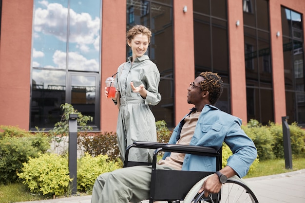 Souriante jolie femme caucasienne avec cocktail d'été gesticulant la main tout en discutant avec son petit ami handicapé pendant la promenade