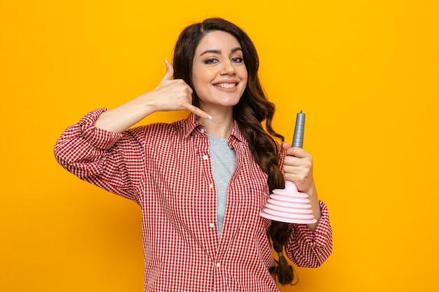 Souriante jolie femme de ménage caucasien tenant un piston en caoutchouc et faisant des gestes, appelez-moi signe