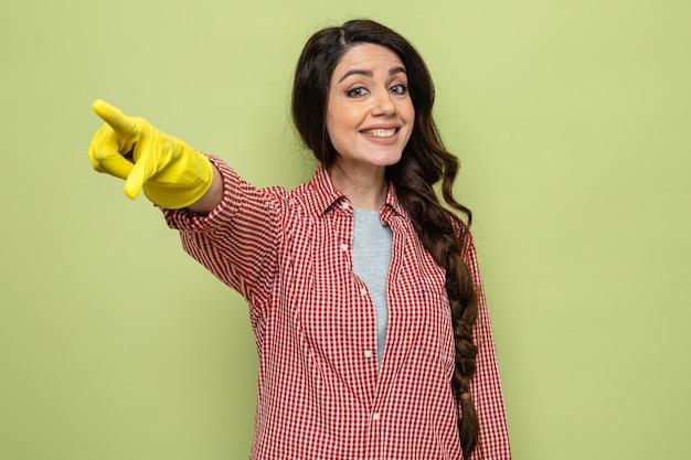 Souriante jolie femme de ménage caucasienne avec des gants en caoutchouc pointant sur le côté et