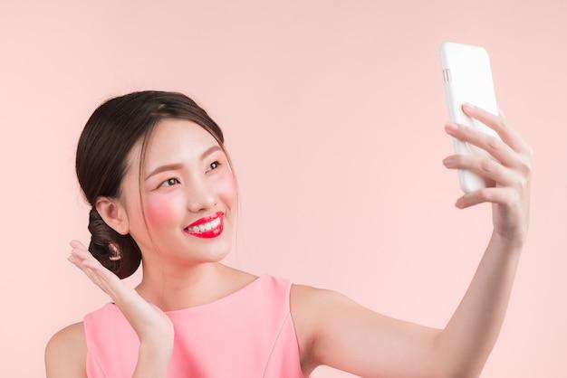 Souriante jolie fille asiatique active prenant une photo de selfie.