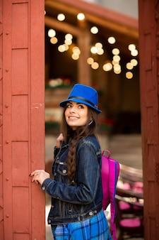 Souriante jolie fille au chapeau bleu près du vieil immeuble avec des portes rouges antiques. modèle féminin pose