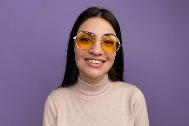 Souriante jolie fille caucasienne brune à lunettes de soleil regarde la caméra sur violet