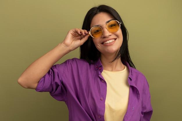 Souriante jolie fille caucasienne brune regarde la caméra à travers des lunettes de soleil sur vert olive