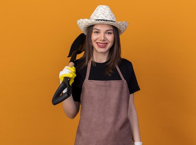 Souriante jolie jardinière caucasienne portant un chapeau de jardinage et des gants tenant une pelle sur l'épaule